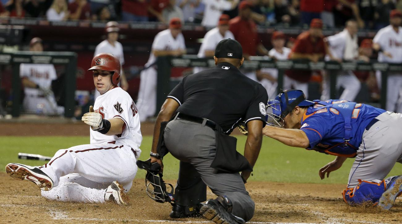 Arizona Diamondbacks' Paul Goldschmidt, left, slides in to score a run ahead of the tag by New York Mets' Anthony Recker, right, as umpire Alan Porter, middle, looks on during the sixth inning of a baseball game Friday, June 5, 2015, in Phoenix. (AP Photo