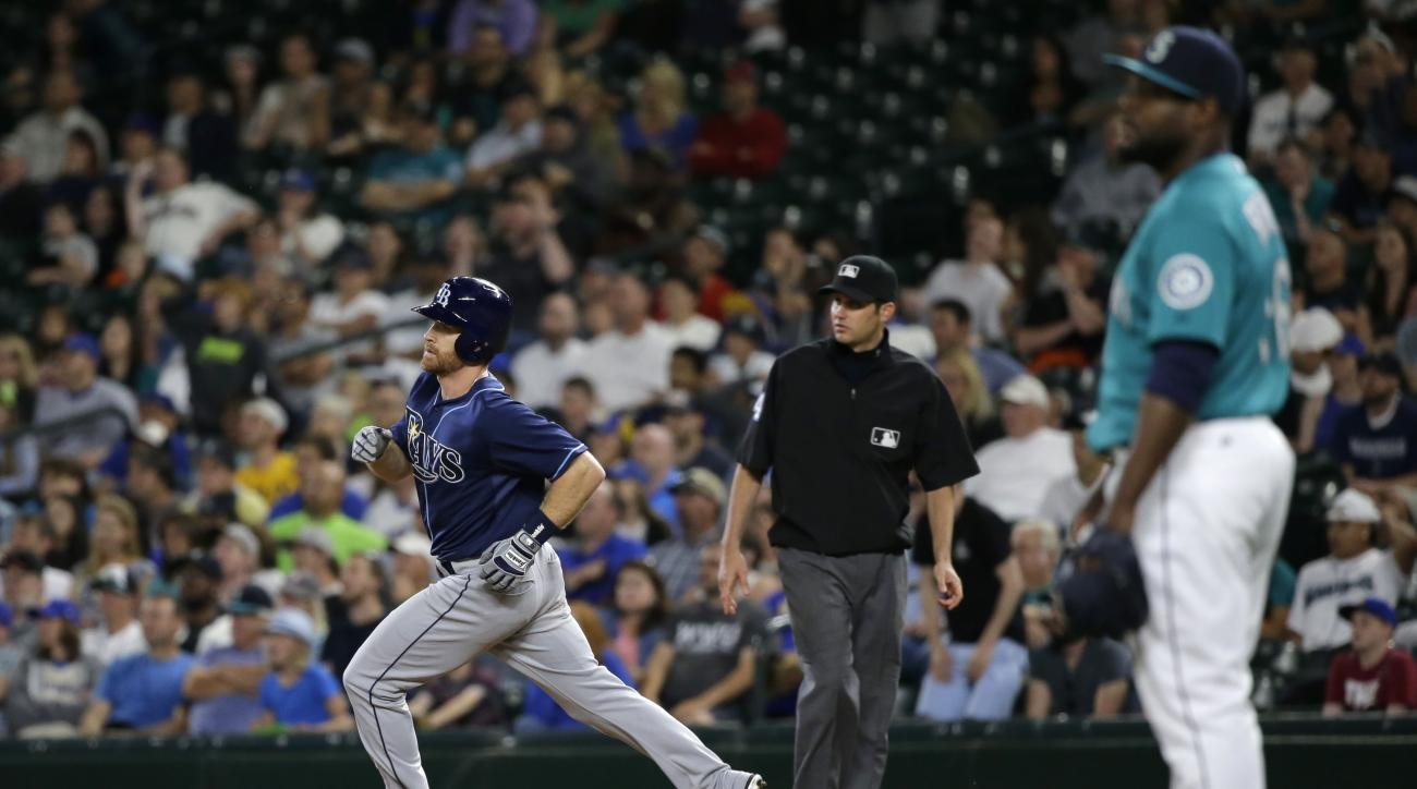 Tampa Bay Rays' Logan Forsythe, left, rounds first base after he hit a solo home run off Seattle Mariners closing pitcher Fernando Rodney, right, in the ninth inning of a baseball game, Friday, June 5, 2015, in Seattle. It was the first run scored by eith