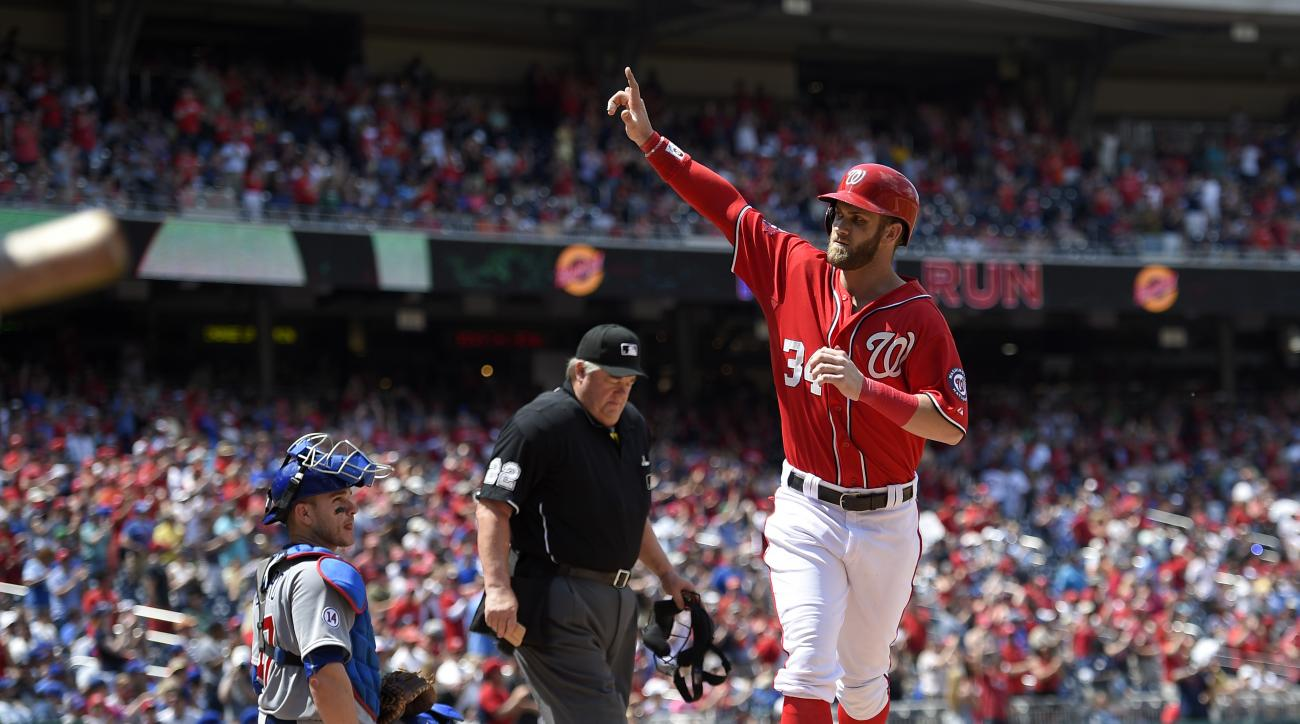 Washington Nationals' Bryce Harper (34) celebrates his home run as Chicago Cubs catcher Miguel Montero, looks on at left, during the ninth inning of a baseball game, Saturday, June 6, 2015, in Washington. The Cubs won 4-2. Also seen is home plate umpire J