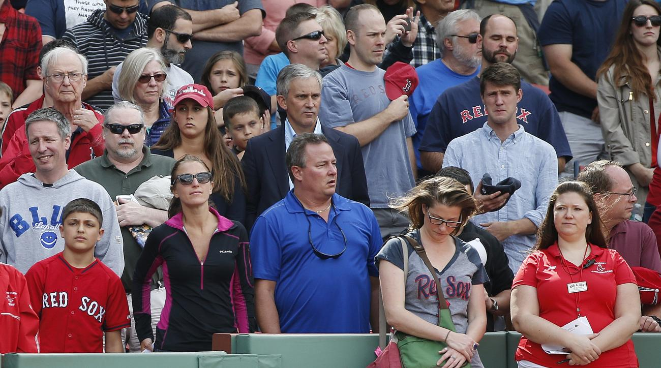 Fans observe a moment of silence before a baseball game between the Boston Red Sox and the Oakland Athletics, at Fenway Park in Boston, Saturday, June 6, 2015, in the area of the stands where a woman was hit and seriously injured by a broken bat during Fr