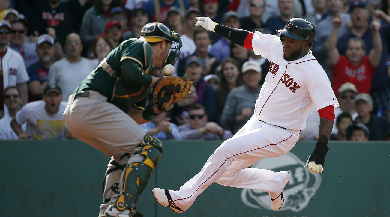 Boston Red Sox's David Ortiz, right, scores on a single by Mike Napoli as Oakland Athletics' Stephen Vogt, left, bobbles the throw during the third inning of a baseball game in Boston, Saturday, June 6, 2015. (AP Photo/Michael Dwyer)