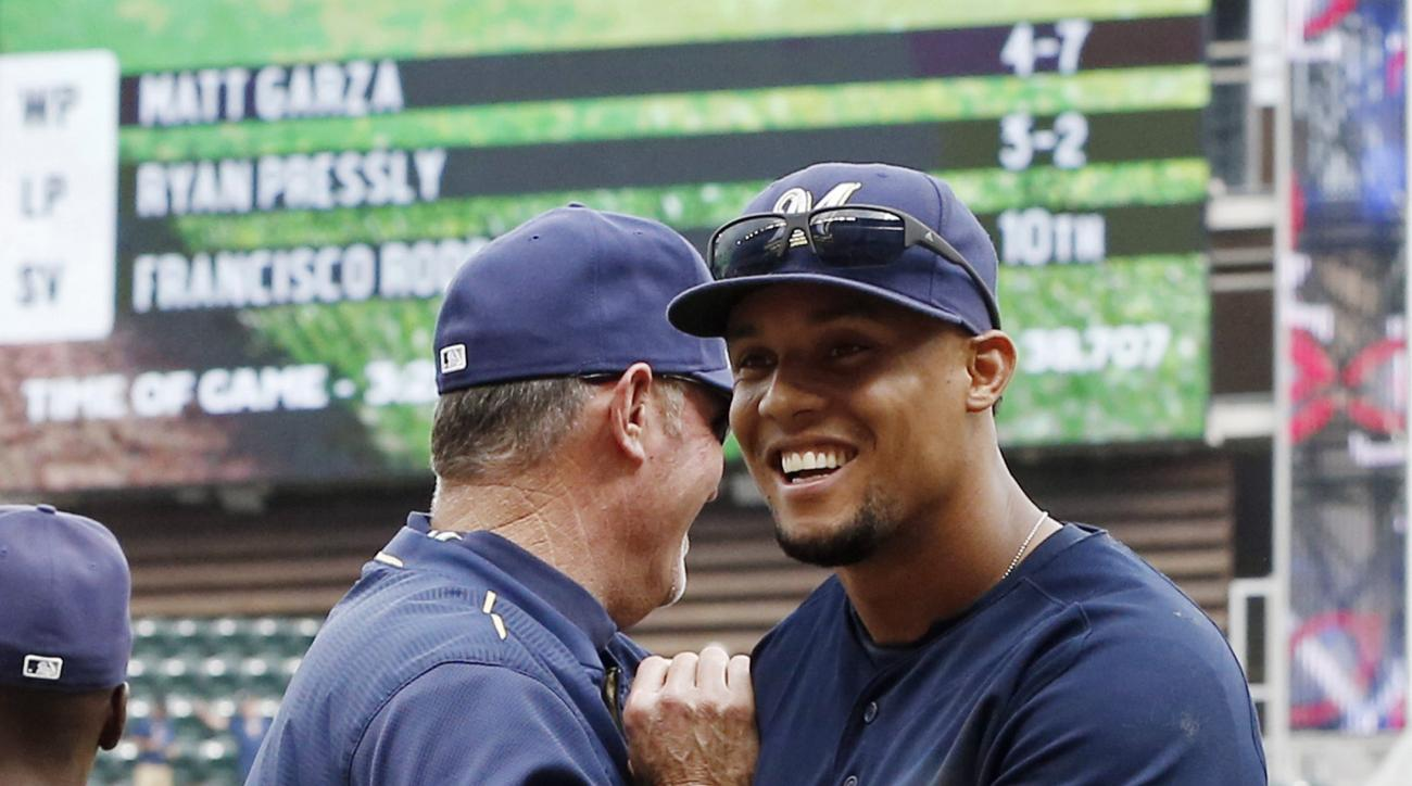 Milwaukee Brewers' Carlos Gomez smiles as he goes through the celebration line after they defeated the Minnesota Twins 4-2 in a baseball game, Saturday, June 6, 2015, in Minneapolis. (AP Photo/Jim Mone)