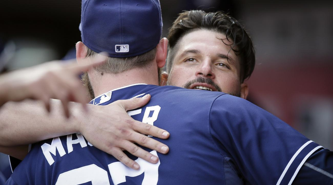 San Diego Padres' Yonder Alonso, right, is hugged in the dugout after hitting a grand slam in the seventh inning of a baseball game against the Cincinnati Reds, Saturday, June 6, 2015, in Cincinnati. (AP Photo/John Minchillo)