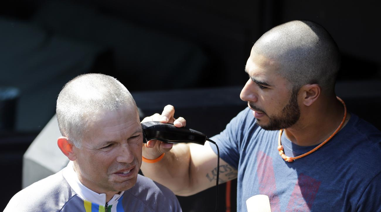 Cleveland Indians' Mike Aviles, right,  shaves Indians owner Paul Dolan's head before the Indians play the Baltimore Orioles in a baseball game, Sunday, June 7, 2015, in Cleveland. Aviles' 4-year-old daughter, Adriana, was diagnosed with leukemia. The Ind