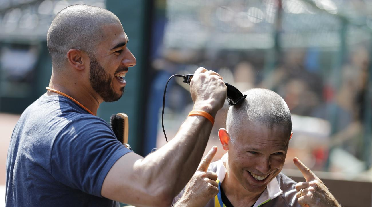Cleveland Indians' Mike Aviles, left, shaves Indians owner Paul Dolan's head before the Indians play the Baltimore Orioles in a baseball game, Sunday, June 7, 2015, in Cleveland. Aviles' 4-year-old daughter, Adriana, was diagnosed with leukemia. The India