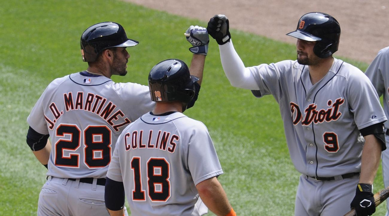 Detroit Tigers  J.D. Martinez, left, gets high-fived by Detroit Tigers Nick Castellanos , right, as Detroit Tigers Tyler Collins looks on after Martinez hit a two run home run during the sixth inning of baseball game against the Chicago White Sox in Chica