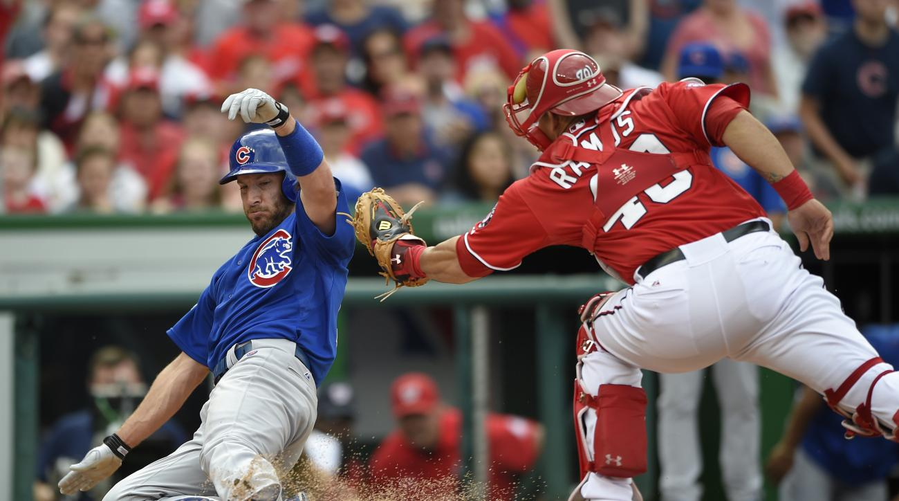 Chicago Cubs' Chris Denorfia, left, slides safely at home to score on a hit by Jonathan Herrera during the fourth inning of a baseball game against Washington Nationals catcher Wilson Ramos (40), Sunday, June 7, 2015, in Washington. (AP Photo/Nick Wass)