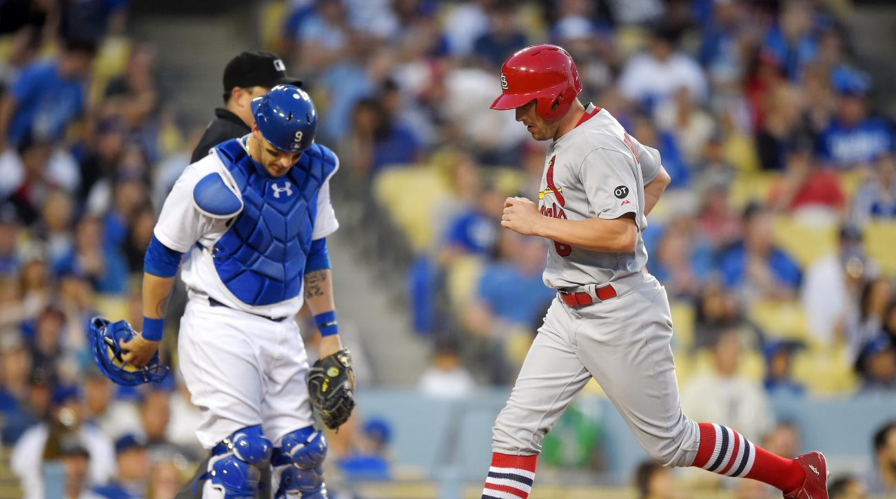St. Louis Cardinals' Peter Bourjos, right, scores on a single by Jhonny Peralta as Los Angeles Dodgers catcher Yasmani Grandal looks down during the eighth inning of a baseball game, Sunday, June 7, 2015, in Los Angeles. (AP Photo/Mark J. Terrill)