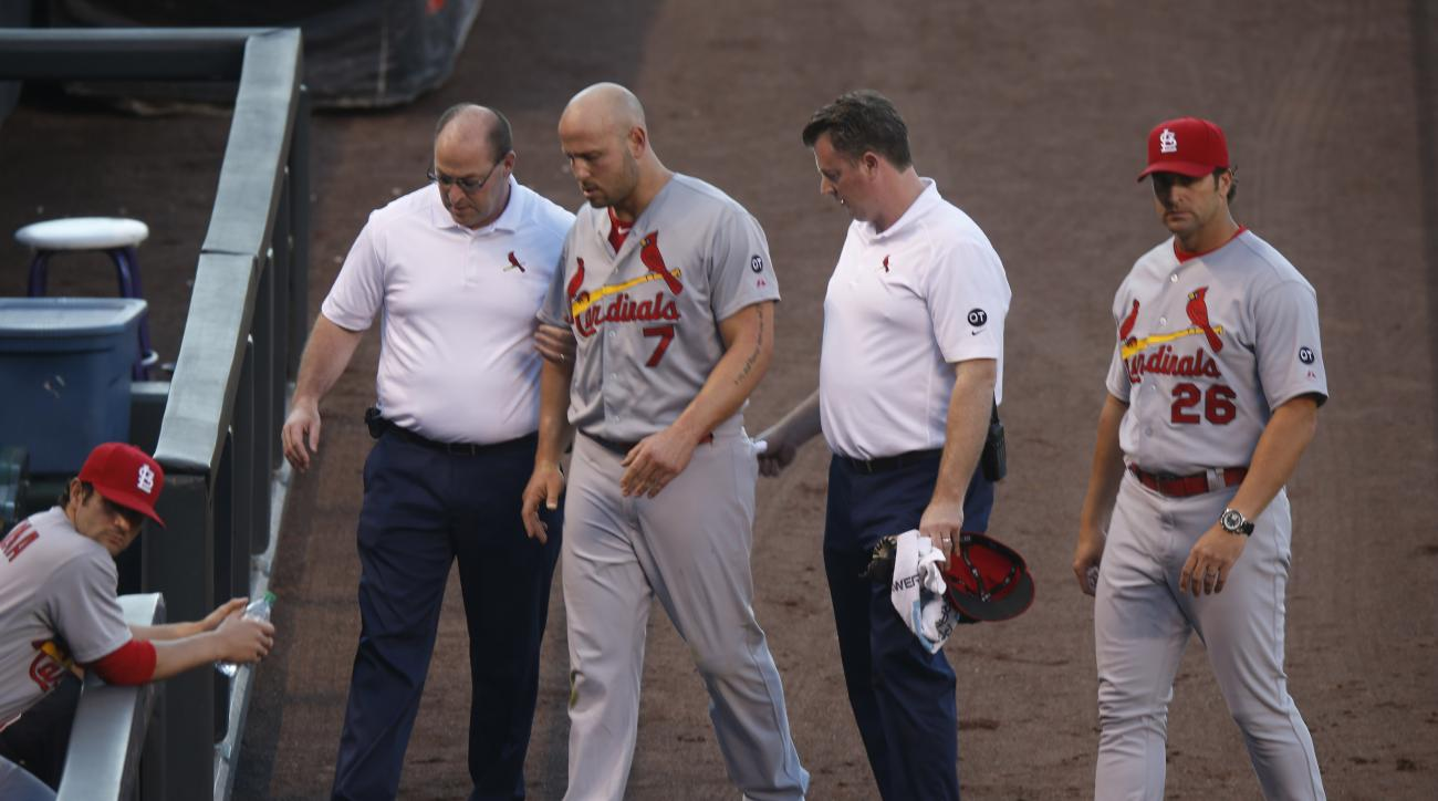 From left, St. Louis Cardinals head trainer Greg Hauck helps left fielder Matt Holliday to the dugout after he injured his leg while pursuing a fly ball against the Colorado Rockies as assistant trainer Chris Conroy and manager Mike Matheny look on in the