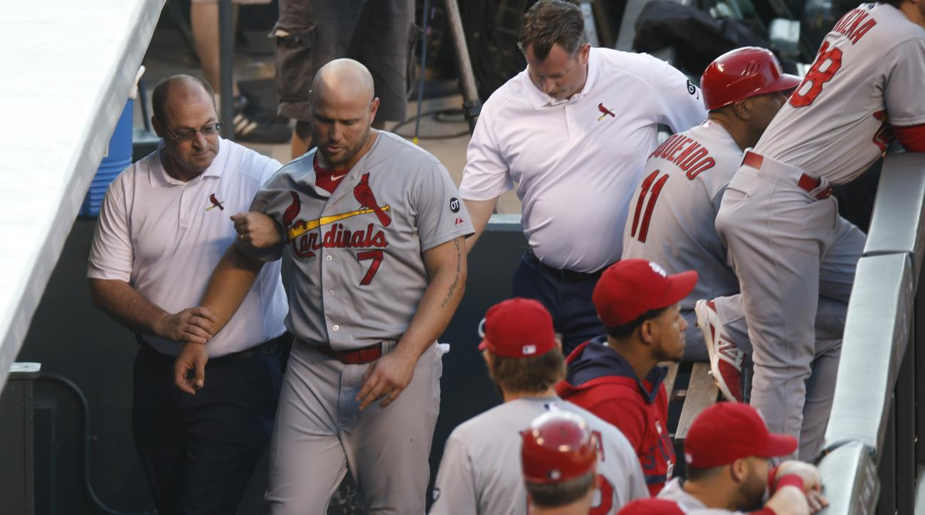 St. Louis Cardinals left fielder Matt Holliday, center, is led through the dugout by head trainer Greg Hauck, left, and assistant trainer Chris Conroy after Holliday hurt his leg while pursuing a fly ball against the Colorado Rockies in the second inning