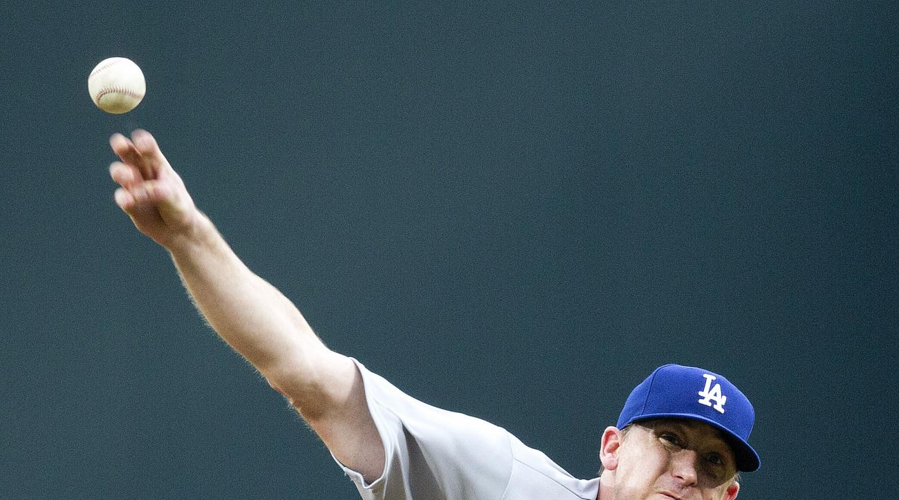 FILE - In this Monday, Aug. 11, 2014 file photo, Los Angeles Dodgers starter Kevin Correia works against the Atlanta Braves in the first inning of a baseball game in Atlanta. The 34-year-old pitcher signed a one-year deal with the Phillies on Monday, June