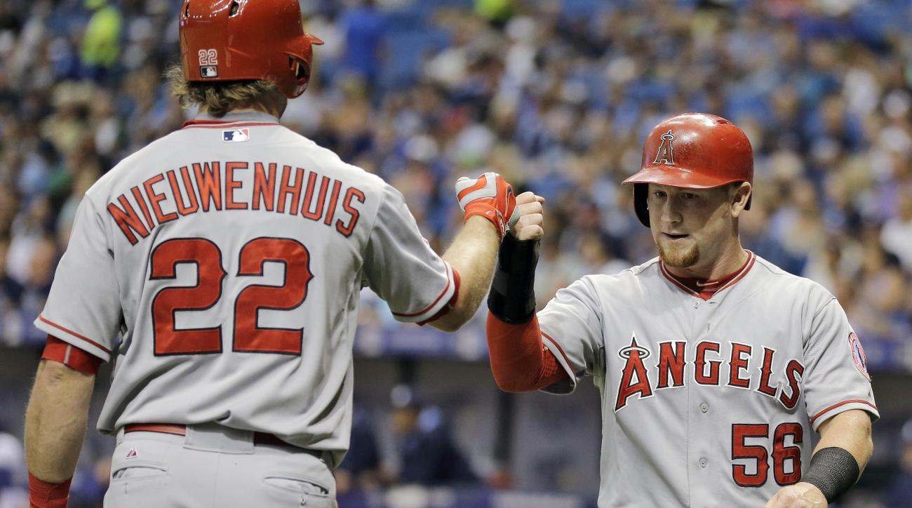 Los Angeles Angels right fielder Kole Calhoun (56) celebrates with teammate Kirk Nieuwenhuis (22) after scoring on an error by Tampa Bay Rays third baseman Jake Elmore during the first inning of a baseball game Tuesday, June 9, 2015, in St. Petersburg, Fl