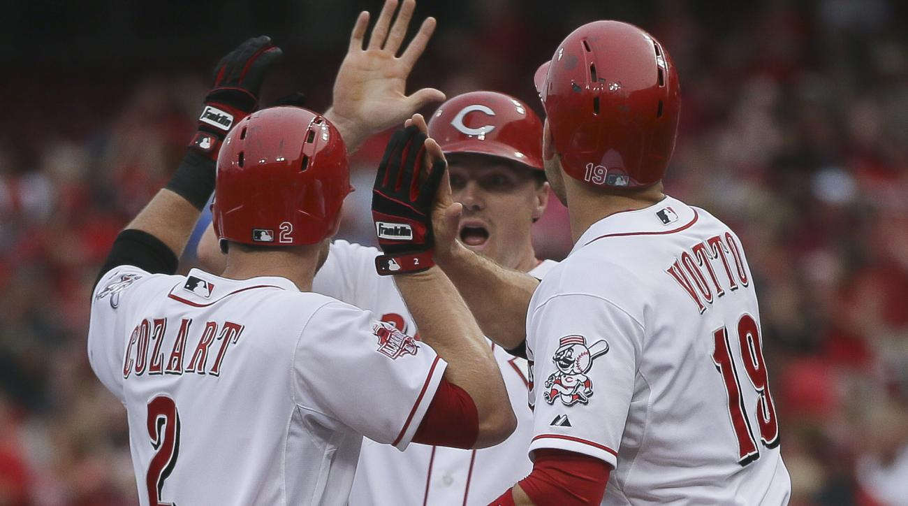 Cincinnati Reds' Zack Cozart (2) celebrates his three-run home run with Jay Bruce, center and Joey Votto (19) during the first inning of a baseball game against the Philadelphia Phillies, Tuesday, June 9, 2015, in Cincinnati. (AP Photo/John Minchillo)