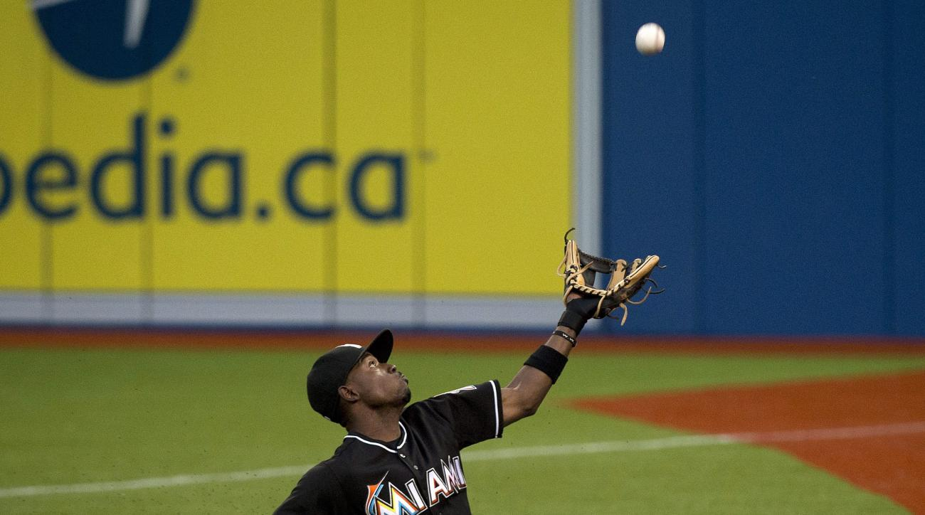 Miami Marlins second baseman Dee Gordon makes a sliding catch on a foul pop fly hit by Toronto Blue Jays' Josh Donaldson during sixth inning interleague baseball action in Toronto on Tuesday, June 9, 2015.  (Nathan Denette/The Canadian Press via AP) MANDA