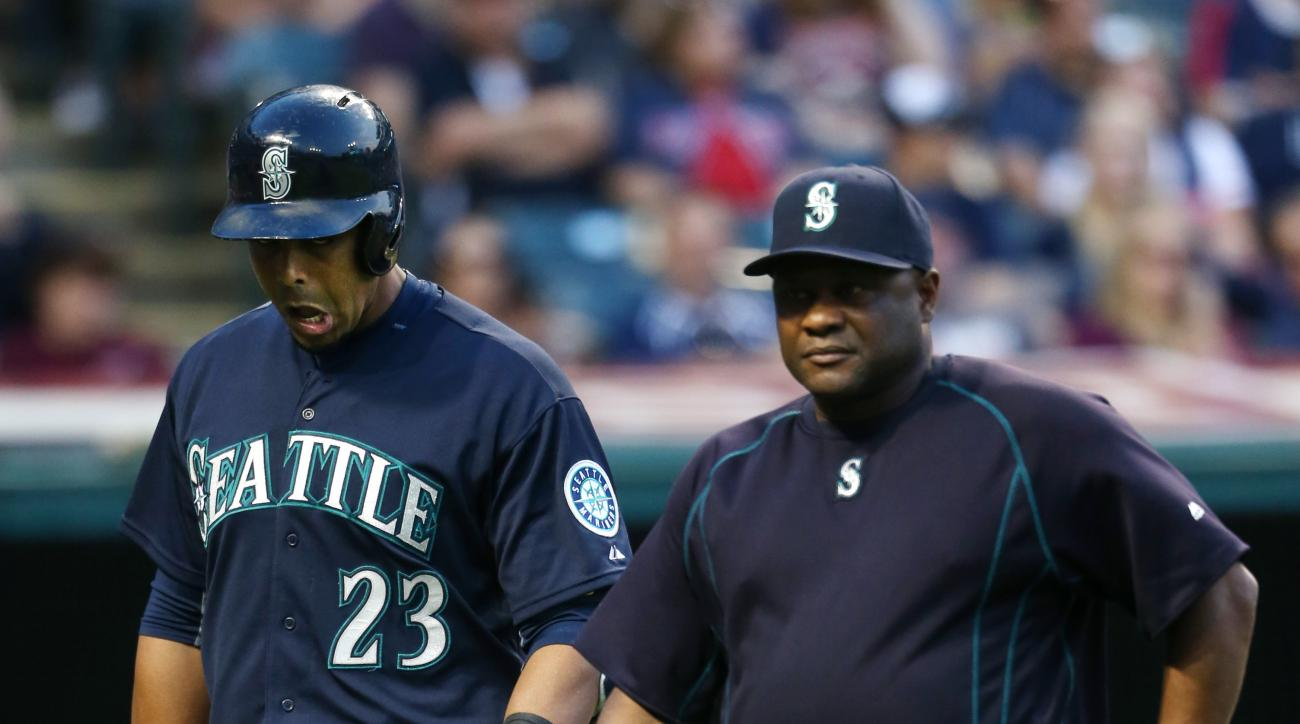 Seattle Mariners Nelson Cruz, left, leaves the game with manager Lloyd McClendon after suffering back spasms during an at bat against the Cleveland Indians during the fifth inning of a baseball game, Tuesday, June 9, 2015, in Cleveland. (AP Photo/Ron Schw