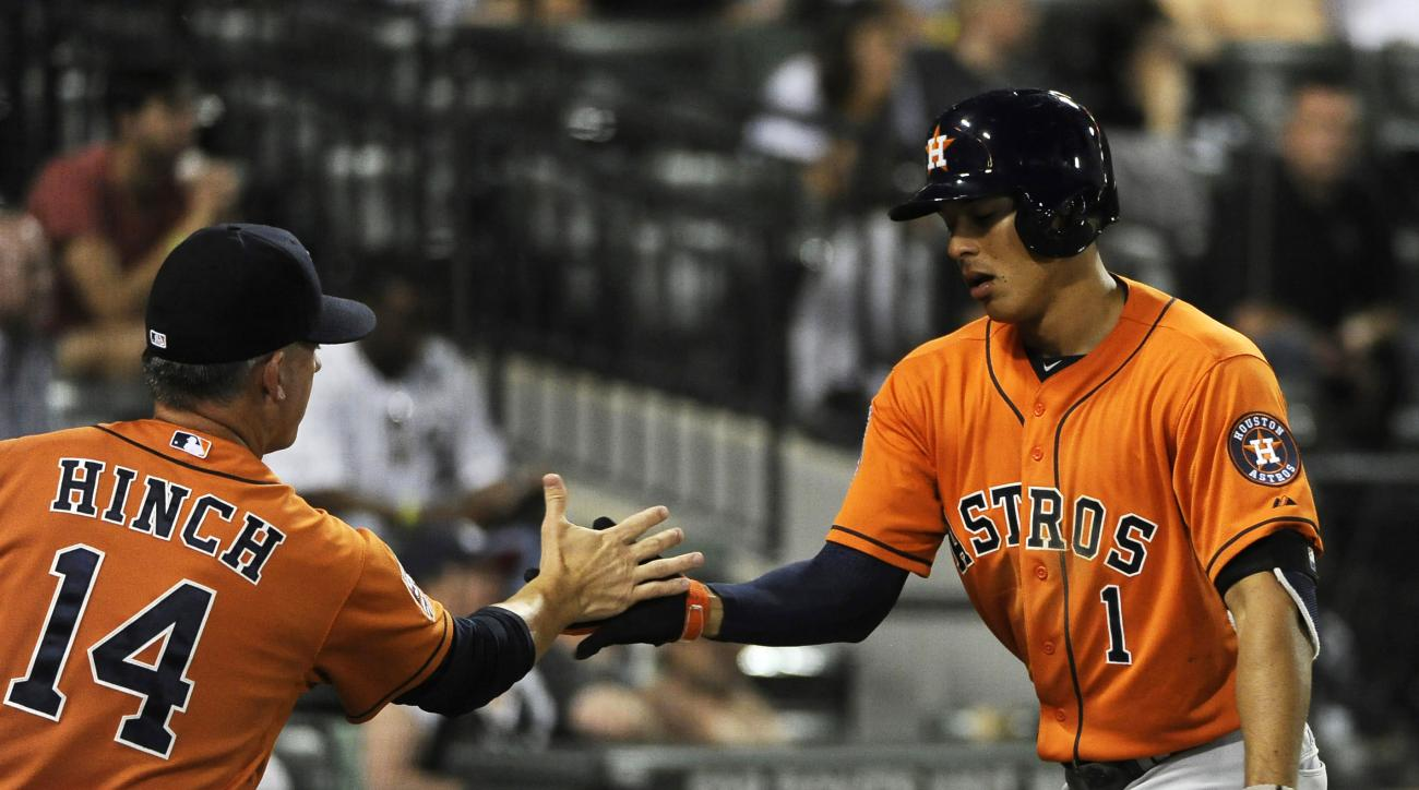 Houston Astros'  Carlos Correa (1) is greeted by manager A.J. Hinch (14) after hitting a two run homer against the Chicago White Sox during the ninth inning of a baseball game,Tuesday, June 9, 2015 in Chicago. (AP Photo/David Banks)