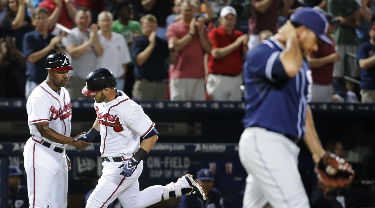 Atlanta Braves' Joey Terdoslavich, center, shakes hands with third base coach Bo Porter after hitting a home run off San Diego Padres relief pitcher Joaquin Benoit, right, in the eighth inning of a baseball game Tuesday, June 9, 2015, in Atlanta. Terdosla