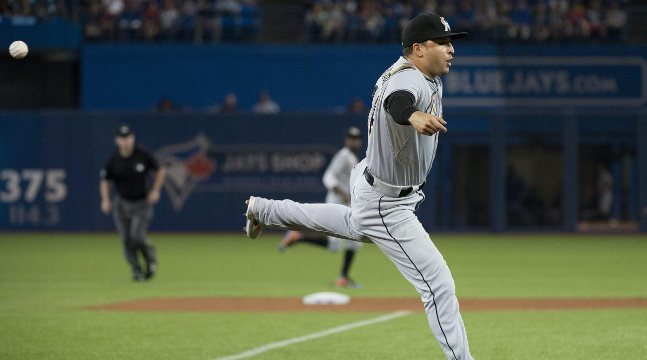 Miami Marlins third baseman Martin Prado misses a bare hand attempt on a single by Toronto Blue Jays' Edwin Encarnacion during the second inning of a baseball game in Toronto, Wednesday, June 10, 2015. (Nathan Denette/The Canadian Press via AP) MANDATORY