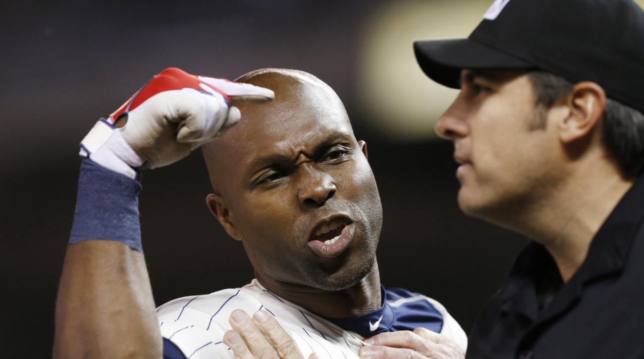 The hands of first base umpire Jeff Kellogg restrain Minnesota Twins' Torii Hunter, left, who argues a call third strike after he was ejected by plate umpire Mark Ripperger during the eighth inning of a baseball game Wednesday, June 10, 2015, in Minneapol