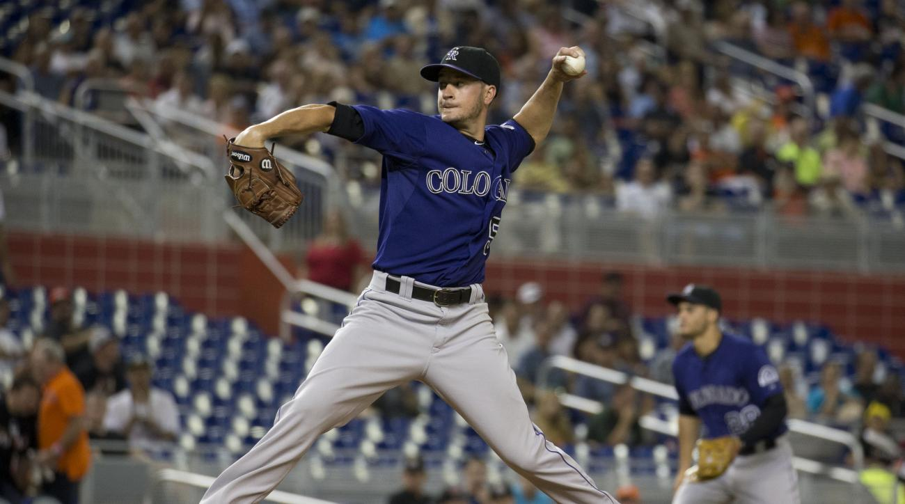 Colorado Rockies starting pitcher Chris Rusin throws to the Miami Marlins during the first inning of a baseball game in Miami, Thursday, June 11, 2015. (AP Photo/J Pat Carter)