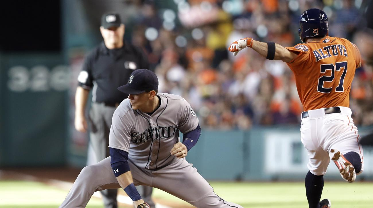 Houston Astros' Jose Altuve (27) beats the throw for a single as Seattle Mariners first baseman Logan Morrison reaches for the ball during the first inning of a baseball game Friday, June 12, 2015, in Houston. (AP Photo/Pat Sullivan)