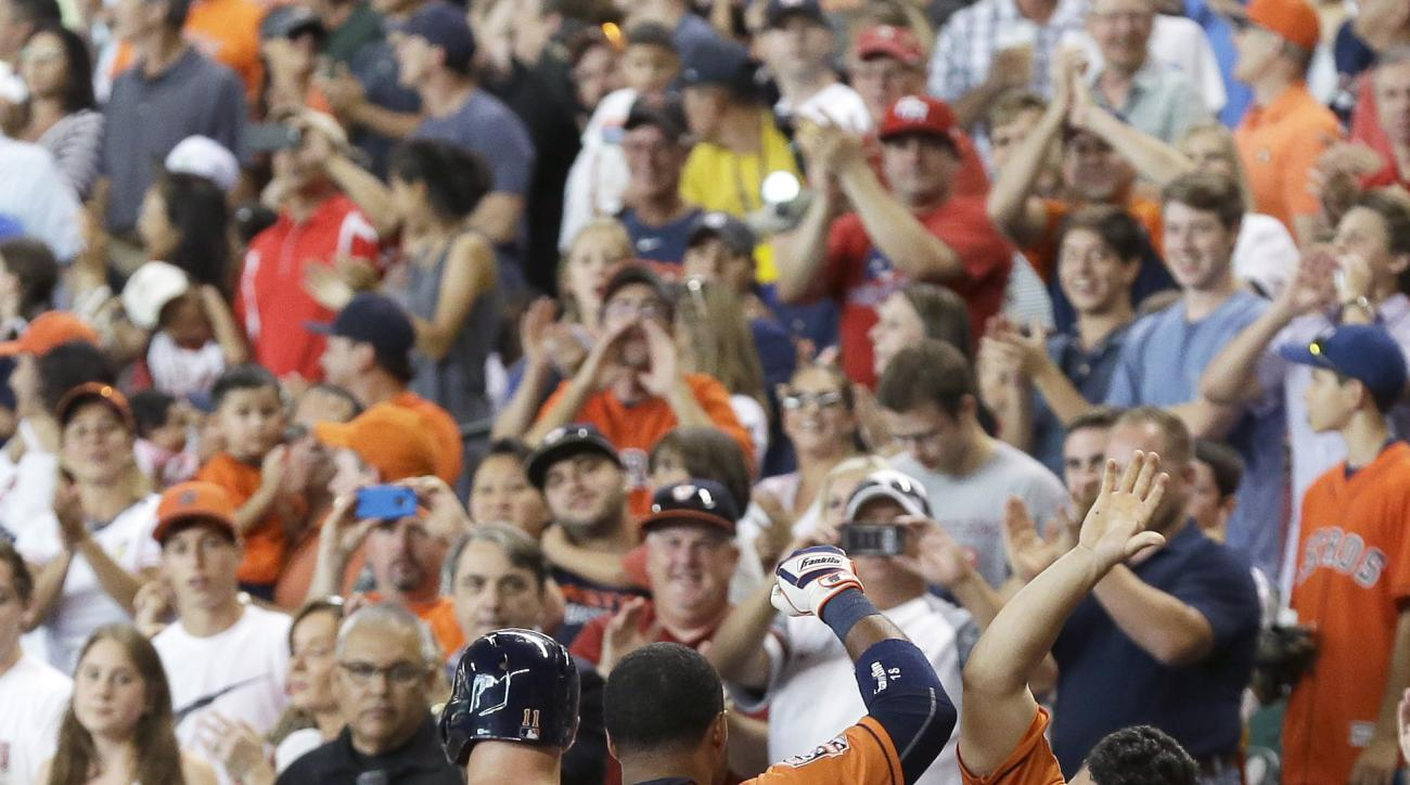 Houston Astros' Luis Valbuena (18) is welcomed back to the dugout by Jose Altuve, right, after hitting a three-run home run against the Seattle Mariners during the first inning of a baseball game Friday, June 12, 2015, in Houston. (AP Photo/Pat Sullivan)