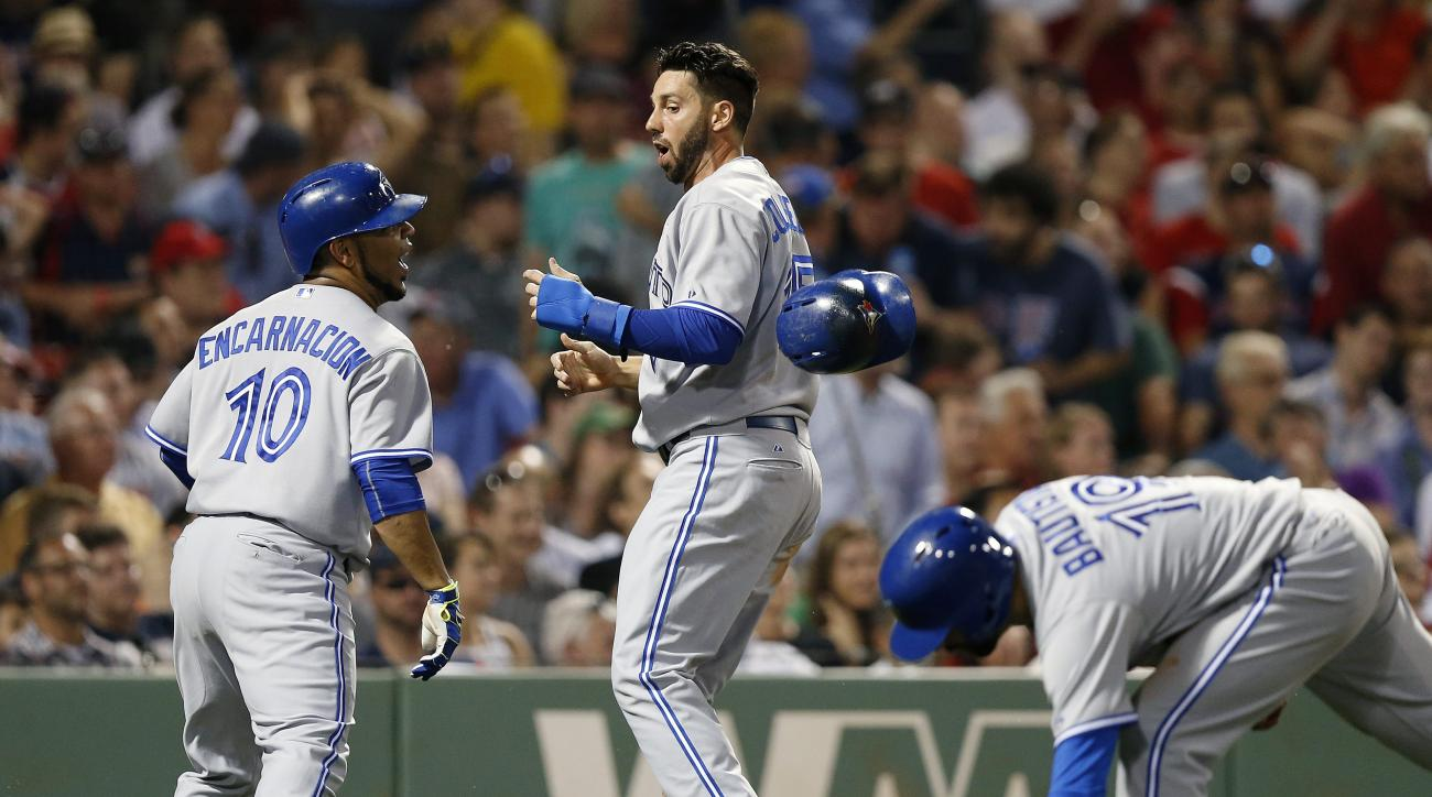 Toronto Blue Jays' Chris Colabello, center, loses his helmet while celebrating after scoring on a triple by Russell Martin that also drove in Edwin Encarnacion (10) and Jose Bautista (19) during the seventh inning of a baseball game against the Boston Red