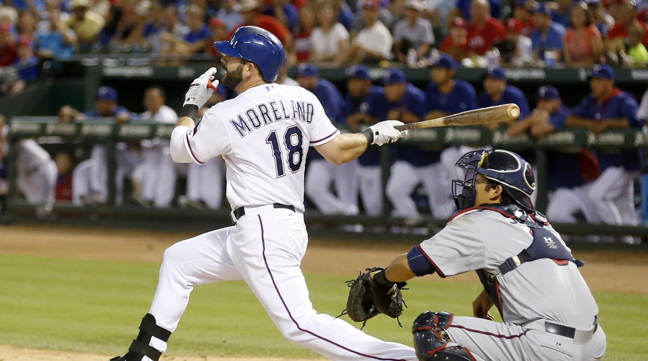 CORRECTS THAT MORELAND REACHED ON ERROR, NOT DOUBLE - Texas Rangers' Mitch Moreland (18) follows through on a ball hit to center field as Minnesota Twins catcher Kurt Suzuki looks on during the eighth inning of a baseball game Friday, June 12, 2015, in Ar