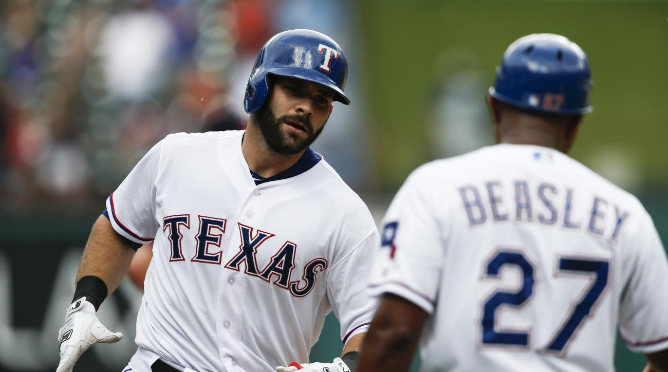 Texas Rangers' Mitch Moreland, left, is congratulated by third base coach Tony Beasley (27) following his three-run home run against the Minnesota Twins during the fourth inning of a baseball game, Saturday, June 13, 2015, in Arlington, Texas. (AP Photo/J