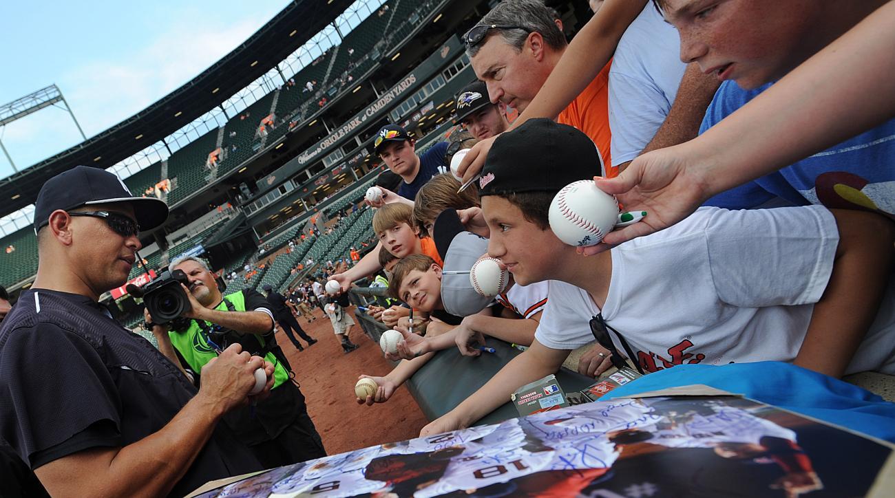 New York Yankees' Alex Rodriguez autographs a baseball before the Yankees' game against the Baltimore Orioles, Saturday, June 13, 2015, in Baltimore. (AP Photo/Gail Burton)