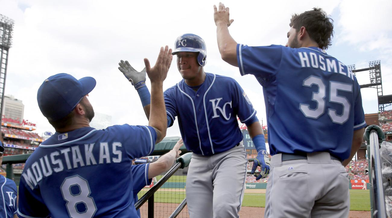 Kansas City Royals' Salvador Perez, center, is congratulated by teammates Mike Moustakas, left, and Eric Hosmer after hitting a solo home run during the fourth inning of a baseball game against the St. Louis Cardinals, Saturday, June 13, 2015, in St. Loui