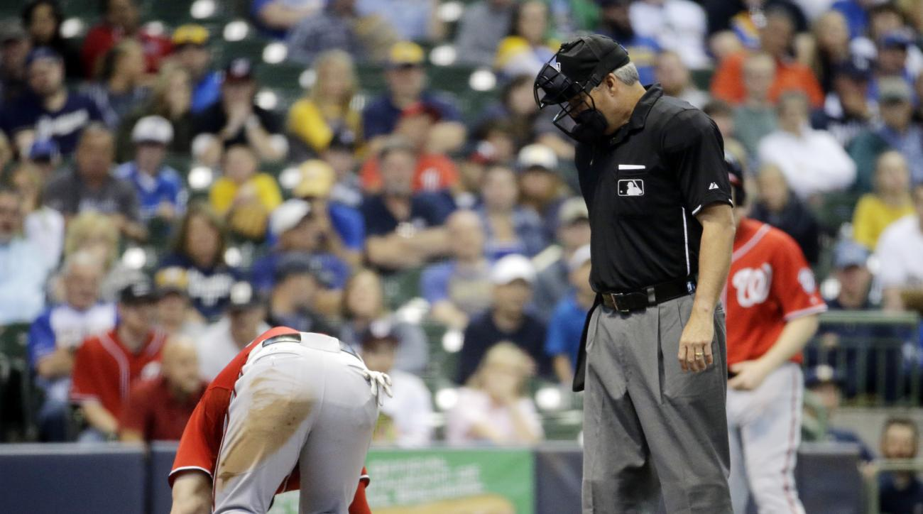 Home plate umpire Tim Timmons watches as Washington Nationals' Bryce Harper reacts after being hit by a pitch during the ninth inning of a baseball game against the Milwaukee Brewers Saturday, June 13, 2015, in Milwaukee. Harper left the game. (AP Photo/M