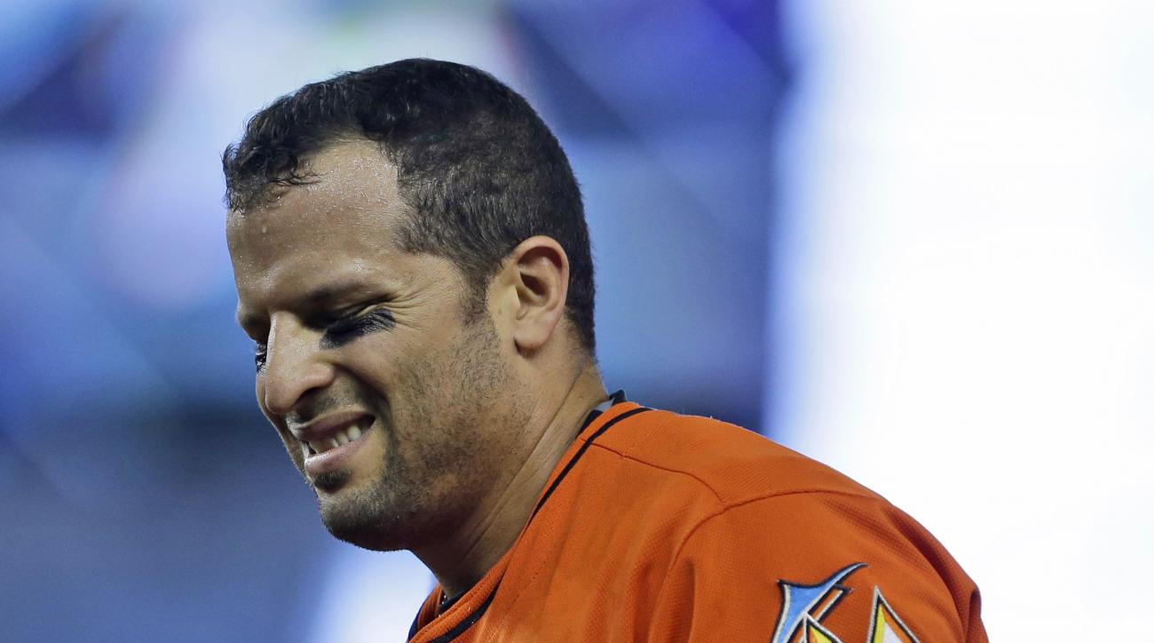 Miami Marlins' Martin Prado heads to the dugout after he was injured reaching first base during the first inning of a baseball game against the Colorado Rockies, Sunday, June 14, 2015, in Miami. (AP Photo/Wilfredo Lee)