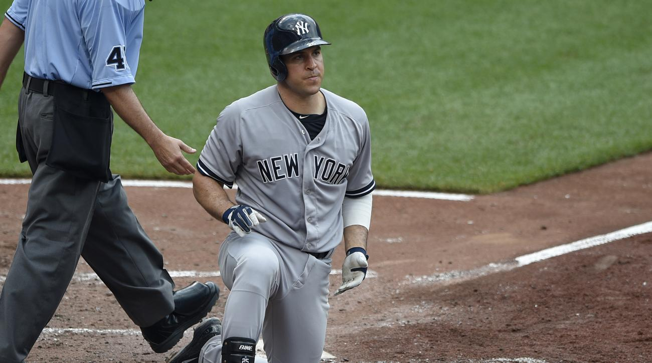 New York Yankees' Mark Teixeira pauses at home plate after he was hit by a pitch by Baltimore Orioles starter Mike Wright during the third inning of a baseball game, Sunday, June 14, 2015, in Baltimore. (AP Photo/Nick Wass)