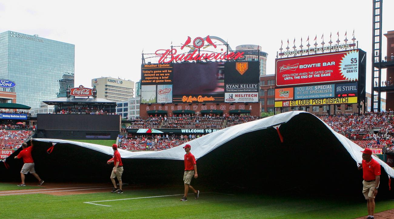 Members of the St. Louis Cardinals grounds crew tarp the field as rain delayed the start of a baseball game against the Kansas City Royals, Sunday, June 14, 2015, in St. Louis. (AP Photo/Scott Kane)