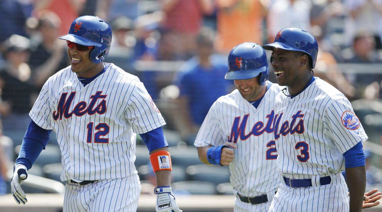 From left, New York Mets' Juan Lagares, Michael Cuddyer, and Curtis Granderson react after scoring on Lagares's sixth-inning, three-run, home run in a baseball game against the Atlanta Braves in New York, Sunday, June 14, 2015. (AP Photo/Kathy Willens)