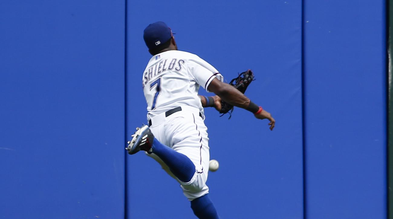 Texas Rangers left fielder Delino DeShields chases the triple hit by Minnesota Twins' Shane Robinson during the sixth inning of a baseball game, Sunday, June 14, 2015, in Arlington, Texas. DeShields was injured on the play. (AP Photo/Jim Cowsert)