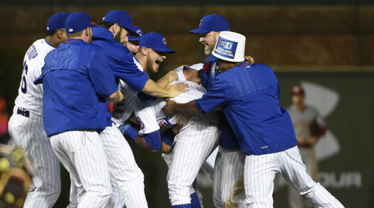 Chicago Cubs' Starlin Castro, center, celebrates his game-winning hit with his teammates against the Cincinnati Reds during the 11th inning of a baseball game, Sunday, June 14, 2015, in Chicago. The Cubs won 2-1. (AP Photo/David Banks)