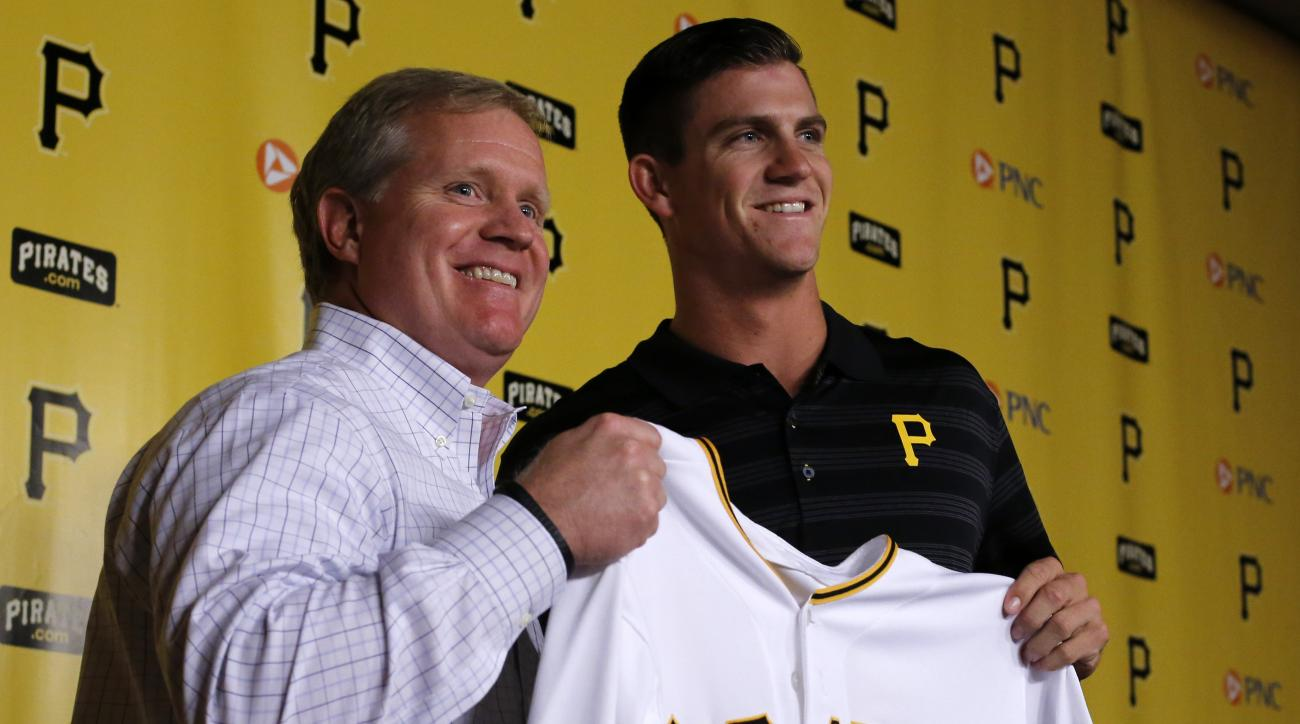 Pittsburgh Pirates general manager Neil Huntington, left, poses with the Pirates first round draft pick, shortstop Kevin Newman, during a news conference before a baseball game between the Pirates and the Chicago White Sox in Pittsburgh, Wednesday, April