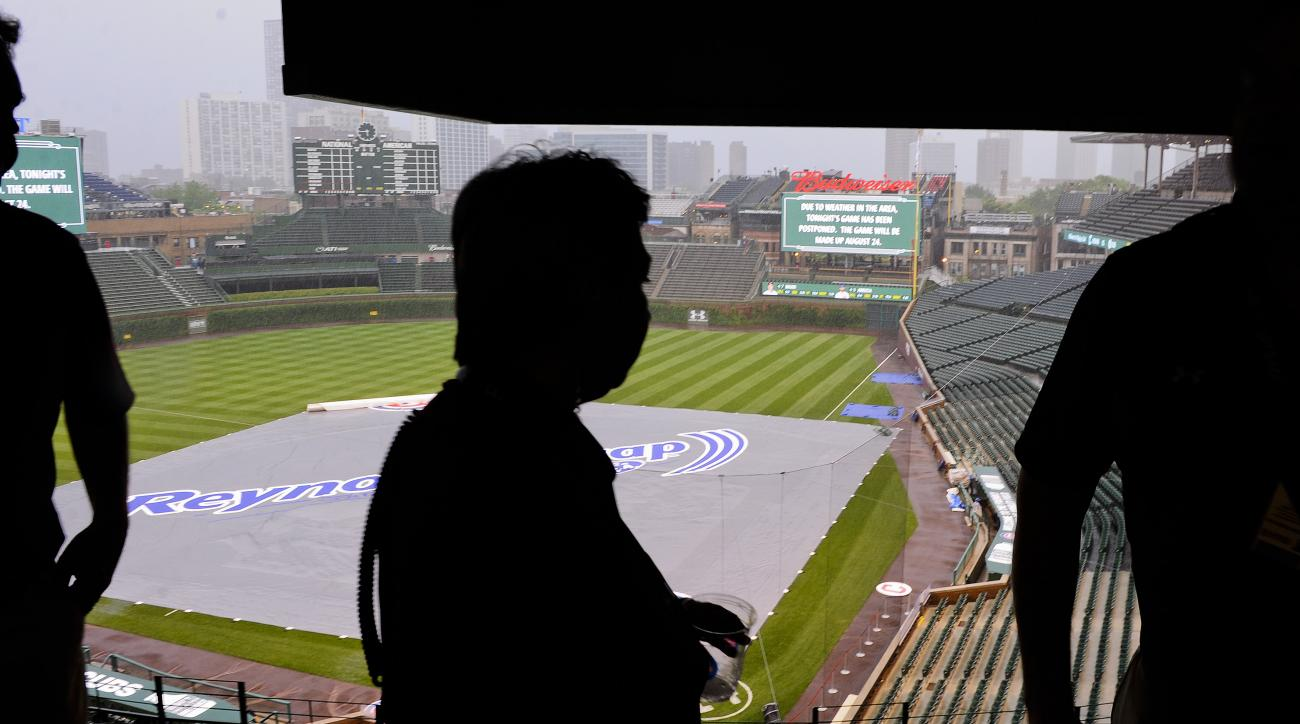 Event supervisors at Wrigley Field look over the field after rain postponed a baseball game between the Chicago Cubs and the Cleveland Indians, Monday, June 15, 2015, in Chicago. (AP Photo/Matt Marton)