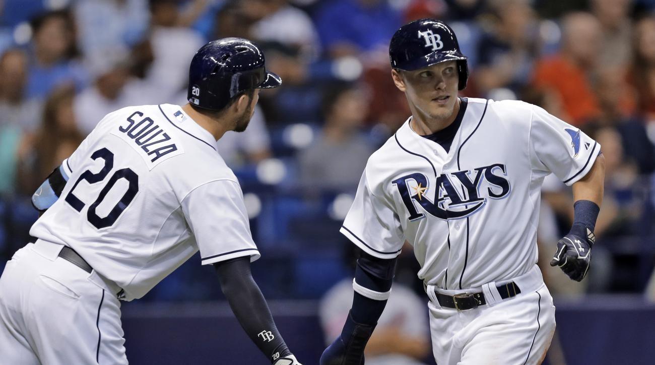 Tampa Bay Rays' Brandon Guyer, right, shakes hands with Steven Souza Jr. after scoring on an RBI single by Logan Forsythe off Washington Nationals starting pitcher Gio Gonzalez during the fourth inning of an interleague baseball game Monday, June 15, 2015