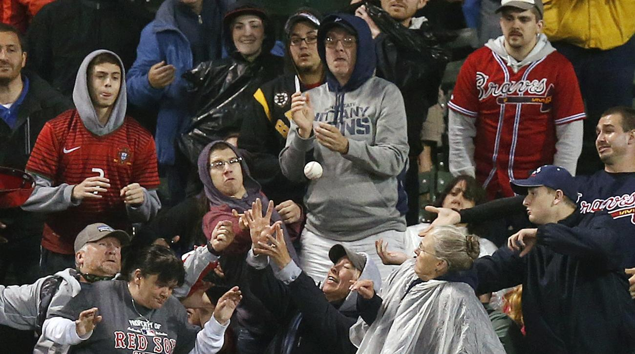 Fans in the center field bleachers reach for the home run ball hit by Boston Red Sox's Xander Bogaerts during the seventh inning of a baseball game against the Atlanta Braves in Boston, Monday, June 15, 2015. (AP Photo/Michael Dwyer)
