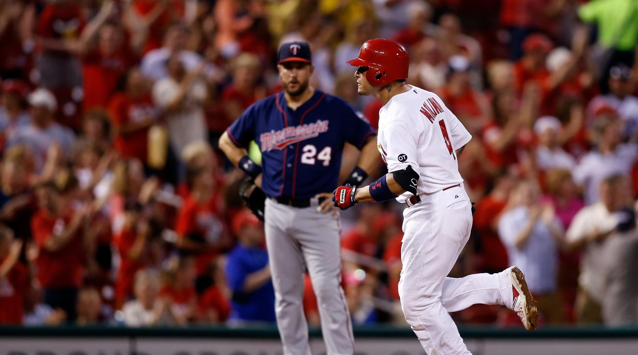 Minnesota Twins third baseman Trevor Plouffe, left, looks on as St. Louis Cardinals' Yadier Molina rounds the bases after hitting a solo home run during the fourth inning of a baseball game Monday, June 15, 2015, in St. Louis. (AP Photo/Scott Kane)
