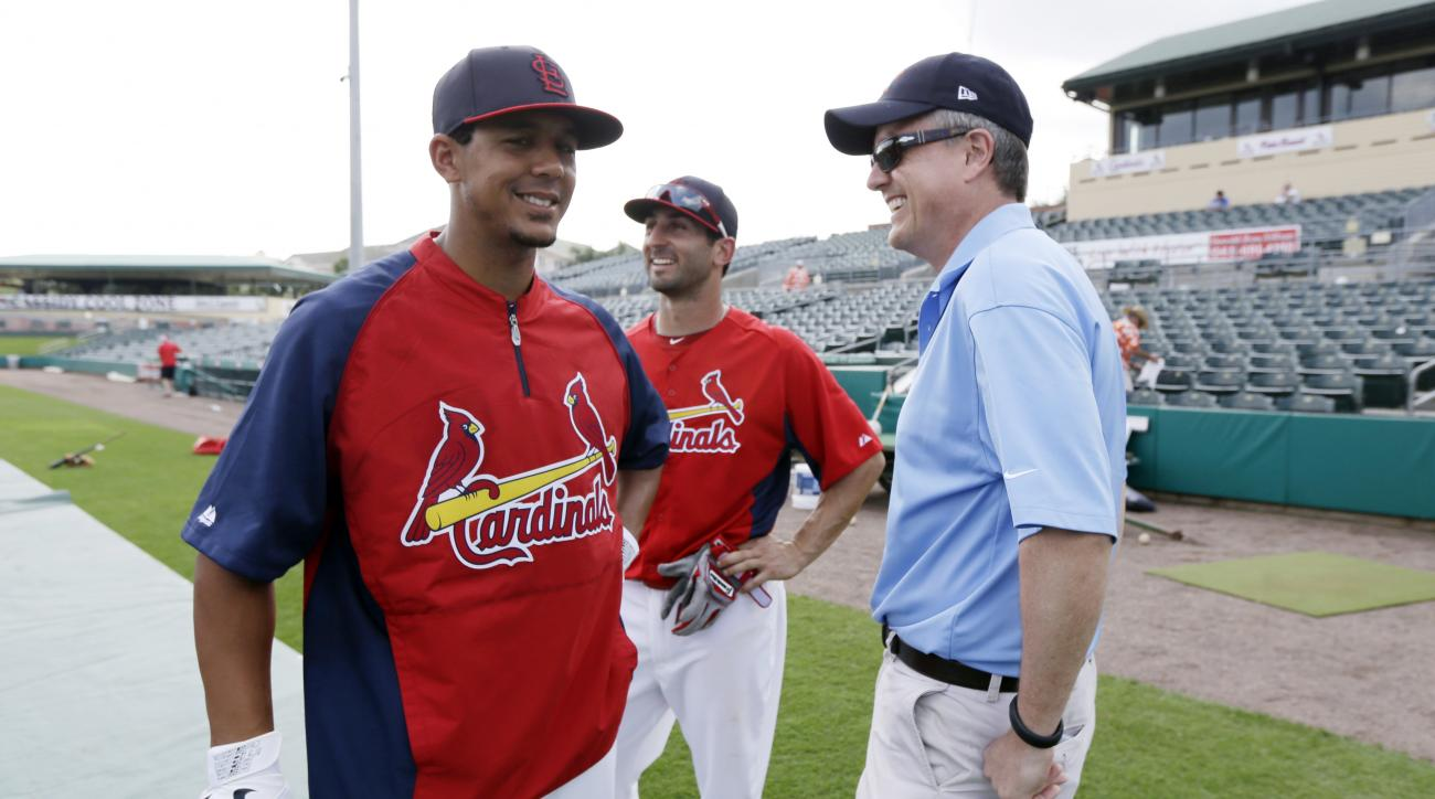 FILE - In this Feb. 25, 2013, file photo, Houston Astros general manager Jeff Luhnow, right, talks to St. Louis Cardinals center fielder Jon Jay, left, and second baseman Daniel Descalso before an exhibition spring training baseball game in Jupiter, Fla.