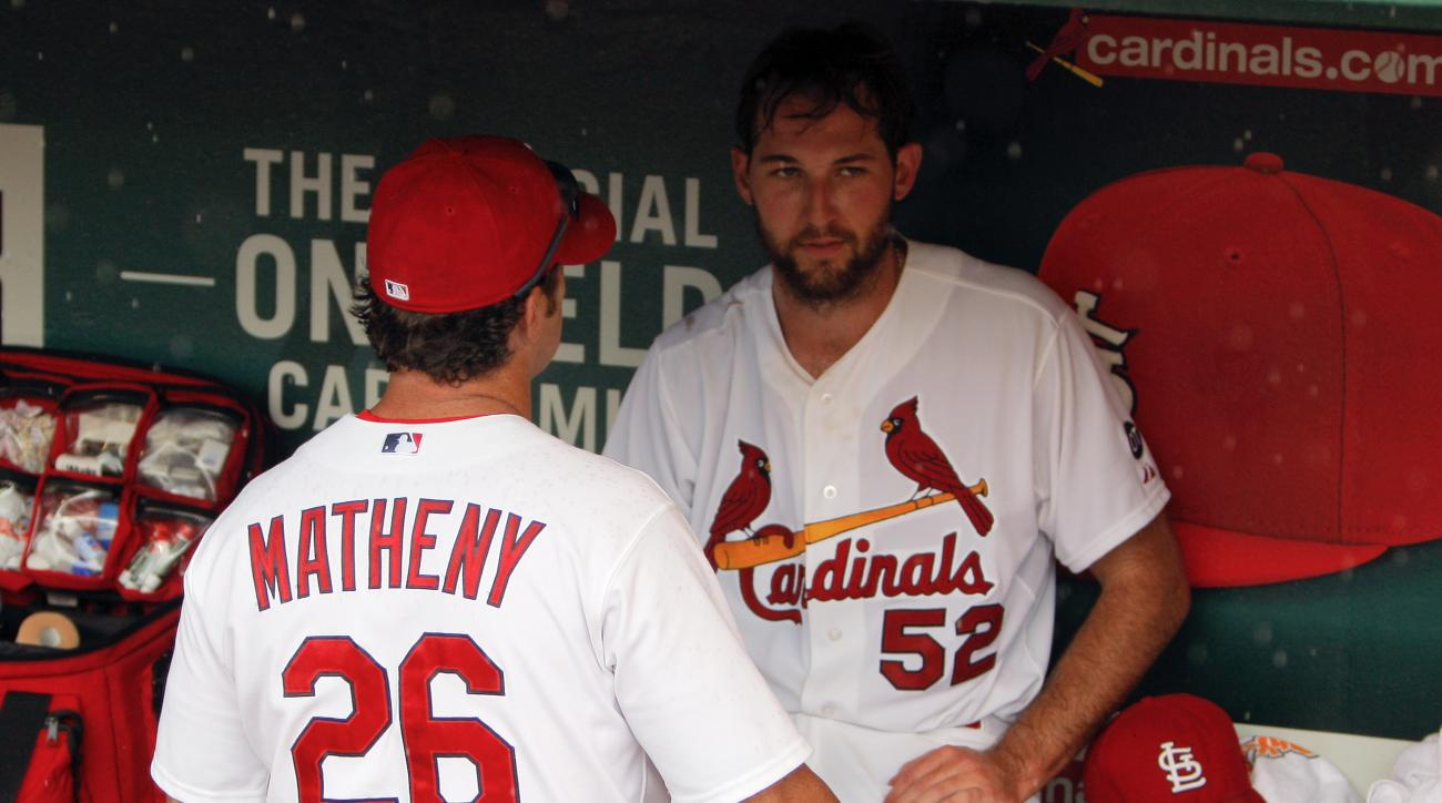 St. Louis Cardinals manager Mike Matheny, left, talks with starting pitcher Michael Wacha in the dugout during a rain delay in the seventh inning of a baseball against the Minnesota Twins, Tuesday, June 16, 2015, in St. Louis. (AP Photo/Scott Kane)