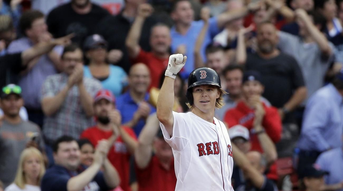 Boston Red Sox's Brock Holt gestures after hitting a triple in the eighth inning of a baseball game against the Atlanta Braves at Fenway Park Tuesday, June 16, 2015, in Boston. Holt hit for the cycle (a single, double, triple and homer) in the baseball ga