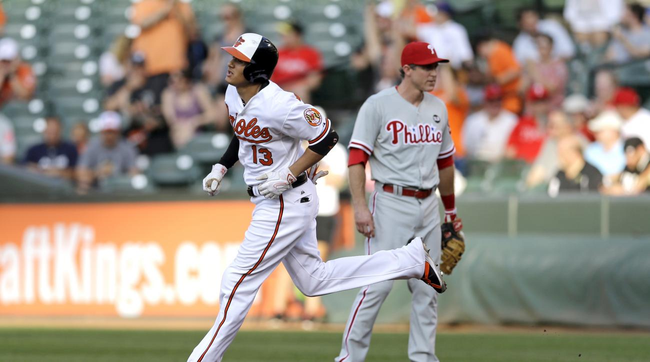 Baltimore Orioles' Manny Machado, left, rounds the bases past Philadelphia Phillies first baseman Chase Utley after hitting a solo home run in the first inning of an interleague baseball game, Tuesday, June 16, 2015, in Baltimore. (AP Photo/Patrick Semans