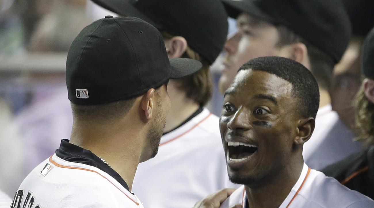 Miami Marlins' Dee Gordon, right, is congratulated by Martin Prado after Gordon scored on a hit by Derek Dietrich during the first inning of a baseball game against the New York Yankees, Tuesday, June 16, 2015, in Miami. (AP Photo/Wilfredo Lee)