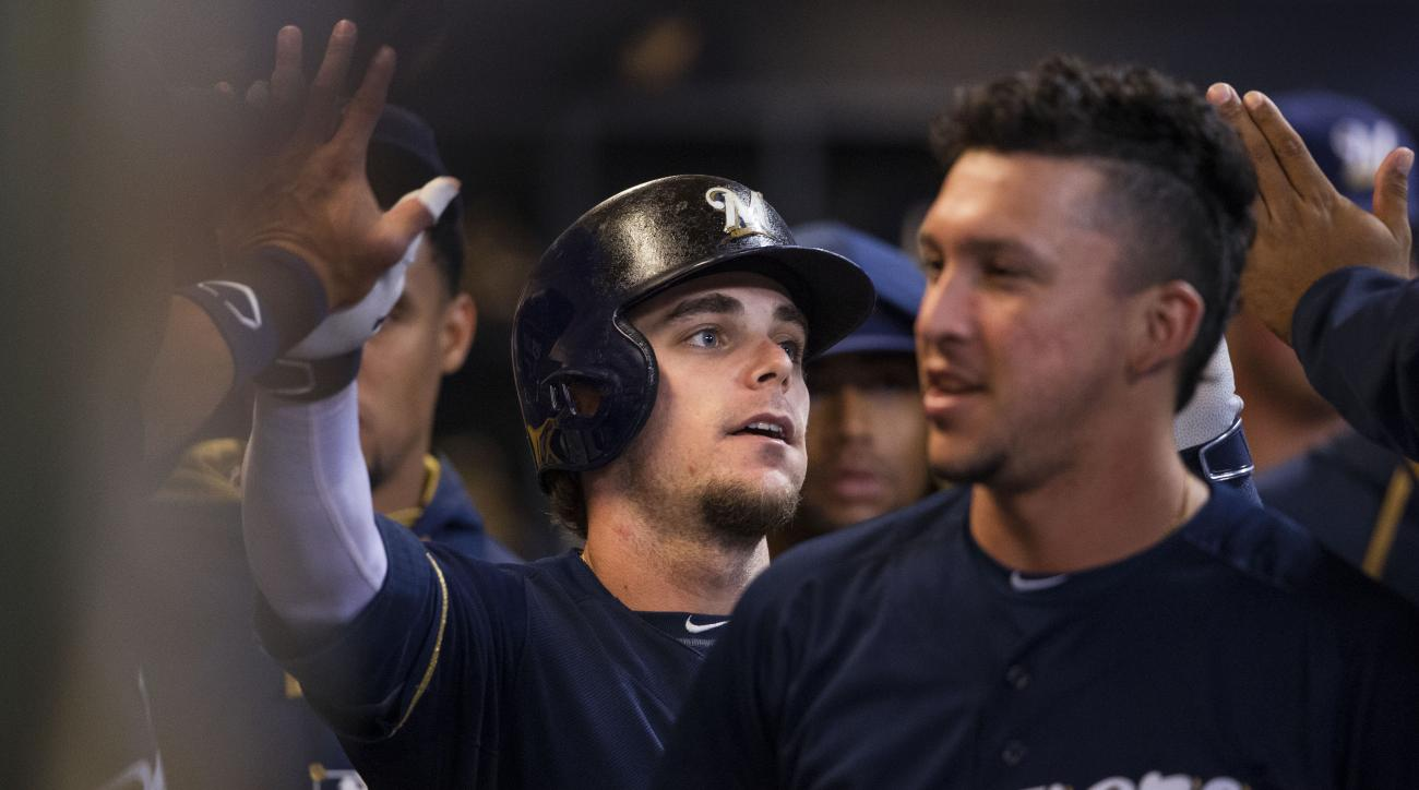 Milwaukee Brewers Scooter Gennett gets some high fives from teammates after hitting a solo home run off of Kansas City Royals' Luke Hochevar  during the ninth inning of a baseball game Tuesday, June 16, 2015, in Milwaukee. The Royals defeated the Brewers