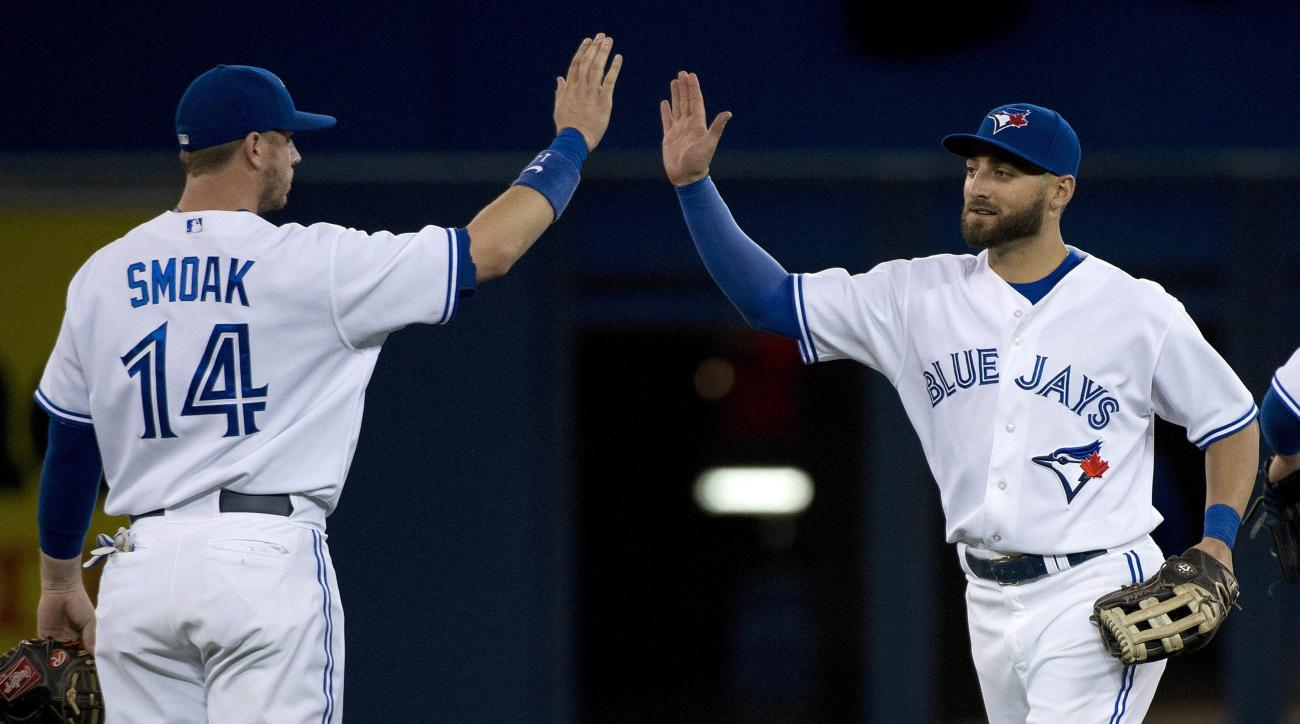 Toronto Blue Jays center fielder Kevin Pillar, right, celebrates with teammate Justin Smoak (14) after defeating the New York Mets in an interleague baseball game, Wednesday, June 17, 2015 in Toronto.  (Nathan Denette/The Canadian Press via AP) MANDATORY
